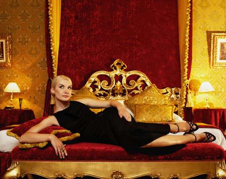 donna ricca: Bella donna sdraiata sul letto in interni di lusso