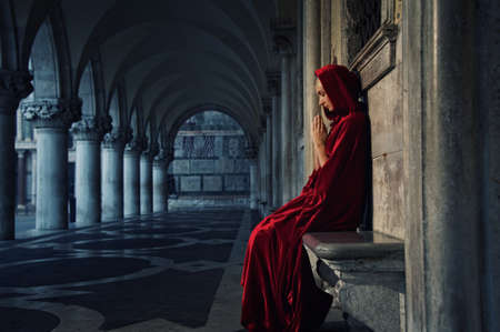 mystery of faith: Woman in red cloak praying alone
