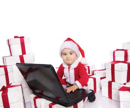 Baby boy in Santa Claus costume  with notebook  photo