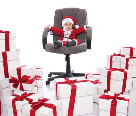 Baby boy in Santa Claus costume sitting on office chair photo
