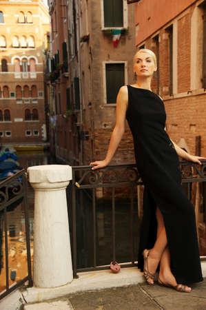 mujeres fashion: Hermosa mujer en vestido negro en un puente Foto de archivo