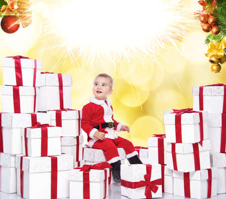 Fireworks above baby boy in Santa Claus costume photo