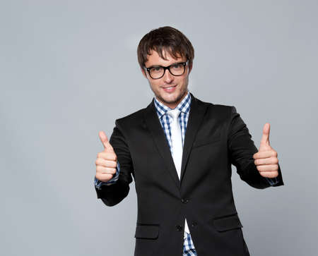 Handsome young man in glasses showing thumbs up photo