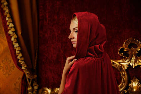 Woman in red hood in luxury interior