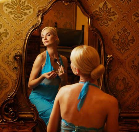 mirar espejo: Mujer de vestido azul reflejado en el espejo Foto de archivo