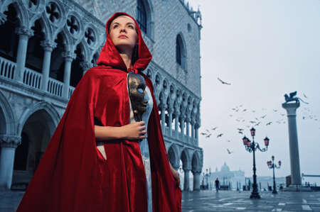 Beautiful woman in red cloak against Dodge's Palace photo