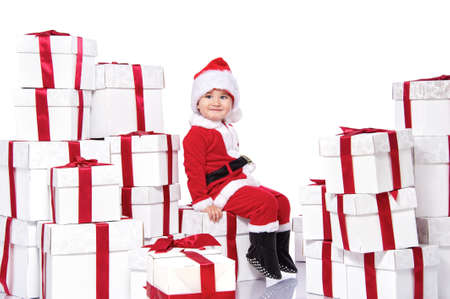 Baby boy in Santa Claus costume sitting on gift boxes photo