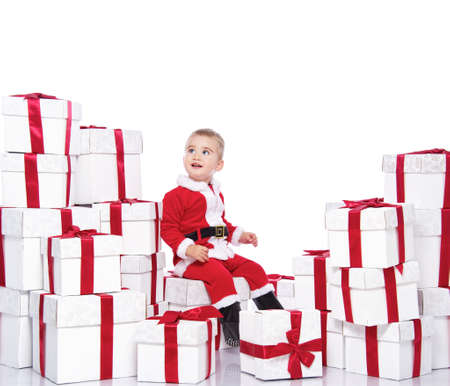 Baby boy in Santa Claus costume sitting on gift boxes Stock Photo - 11384843