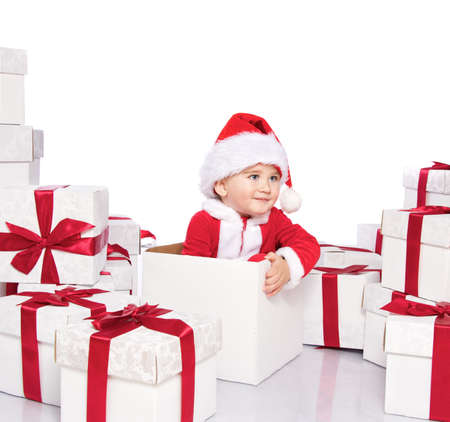 Baby boy in Santa Claus costume sitting inside gift box photo