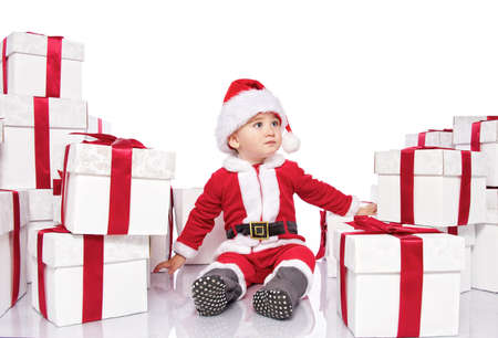 Baby boy in Santa Claus costume sitting between gift boxes photo