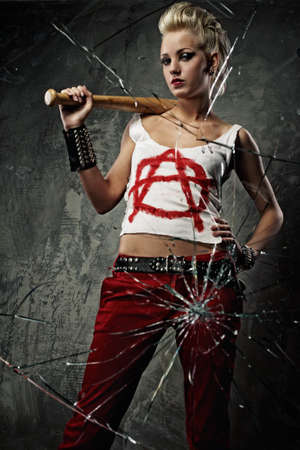 anarchy: Punk girl with a bat behind broken glass Stock Photo
