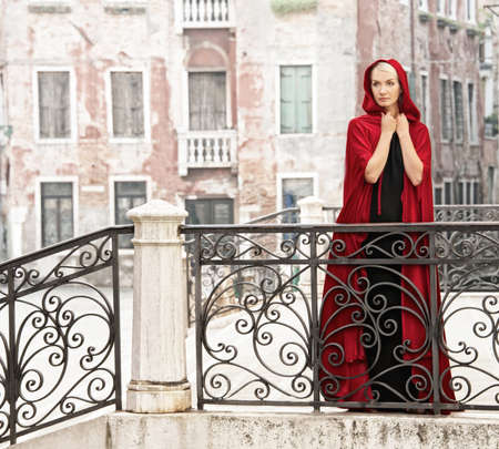 Beautiful woman in red cloak on a bridge. photo