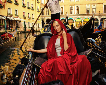 Beautifiul woman in red cloak riding on gandola photo