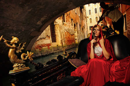 venice carnival: Beautifiul woman in red cloak riding on gandola