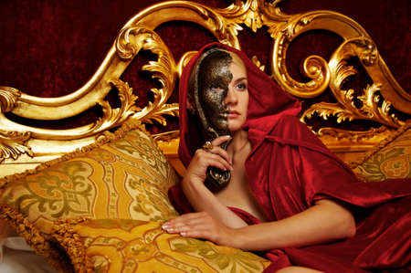 Beautiful woman with a carnival mask lying on bed photo