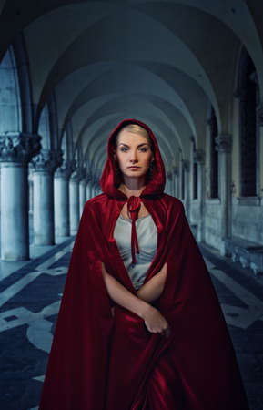 Beautiful woman in red cloak outdoor photo