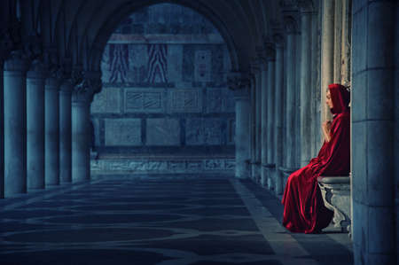 Woman in red cloak praying alone Stock Photo - 11940373