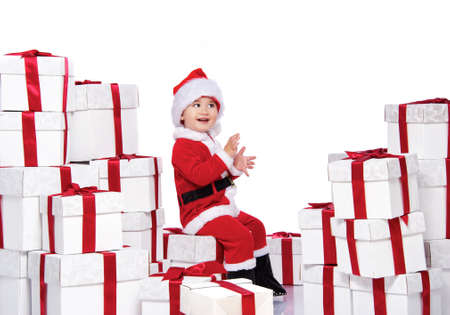 Baby boy in Santa Claus costume sitting on gift boxes Stock Photo - 11395684