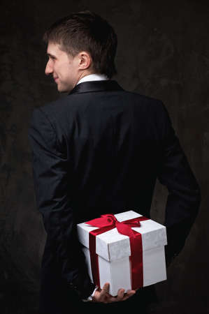 Young man hiding a gift box behind his back. photo