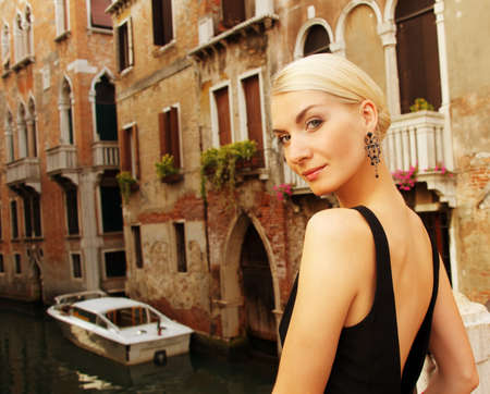 Blond lady against Venice canal. photo