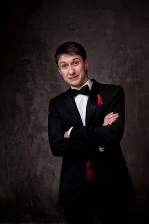 Funny young man wearing tuxedo. photo