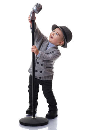 sings: Baby boy with a microphone. Stock Photo