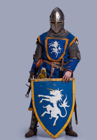 Åšredniowieczny rycerz na szarym tle.