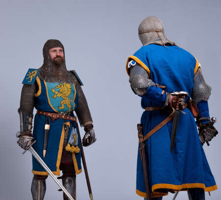 blue grey coat: Two medieval knights preparing to fight.