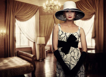 fascinating: Beautiful woman in hat in luxury room.