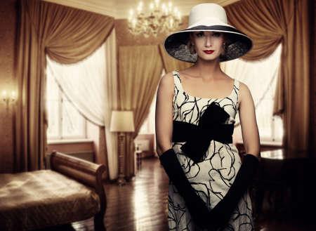 mujer elegante: Hermosa mujer en el sombrero en la habitación de lujo.