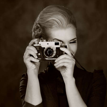 Woman in classic dress with retro camera. photo