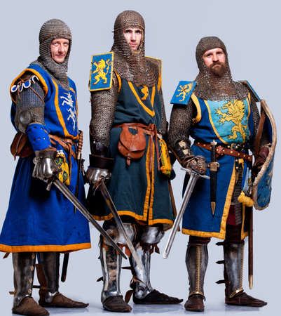 chain armour: Three medieval knights isolated on grey background.