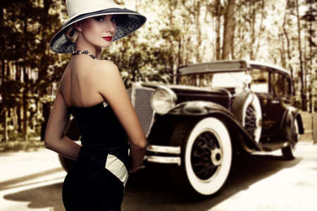 classic car: Woman in hat against retro car. Stock Photo