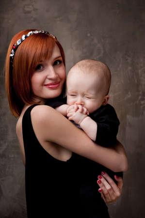 mom holding baby: Beautiful redhead woman with her child. Stock Photo