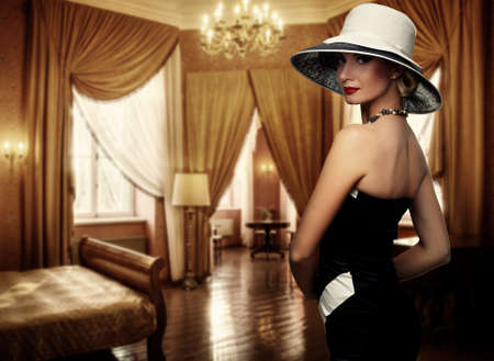 hotel: Beautiful woman in hat in luxury room.
