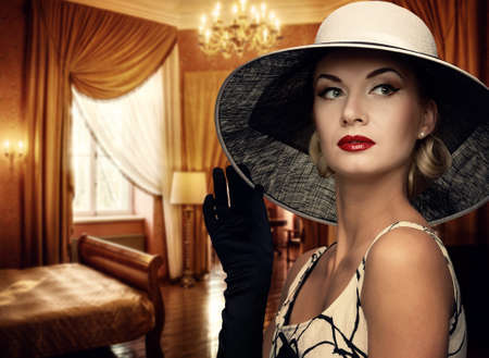 elegance: Beautiful woman in hat in luxury room.