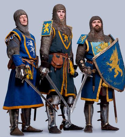 espadas medievales: Tres caballeros medievales sobre fondo gris. Foto de archivo