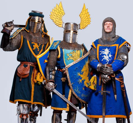 crusades: Three medieval knights isolated on grey background.