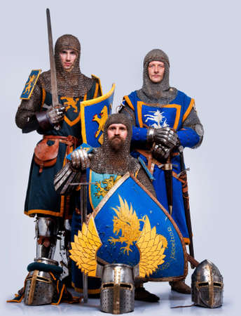 Three medieval knights isolated on grey background. photo