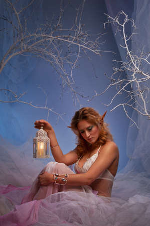 Elf in magical winter forest with lantern. Stock Photo - 12221671