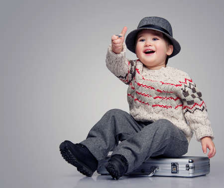 Smiling baby boy sitting on a suitcase. photo