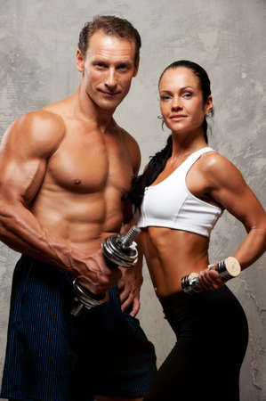 Athletic man and woman with a dumbbells. Stock Photo - 12221667