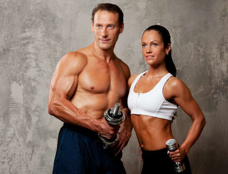 barbell: Athletic man and woman with a dumbbells.