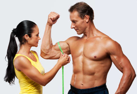 Woman measuring athletics man biceps. photo