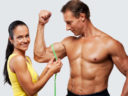 Woman measuring athletics man biceps. photo