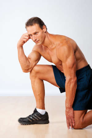 Handsome muscular man doing fitness exercise. Stock Photo - 12221620