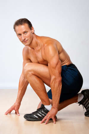 Handsome muscular man doing fitness exercise. photo