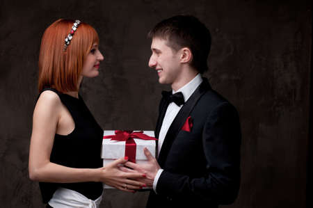 birthday suit: Beautiful young couple with a gift box.