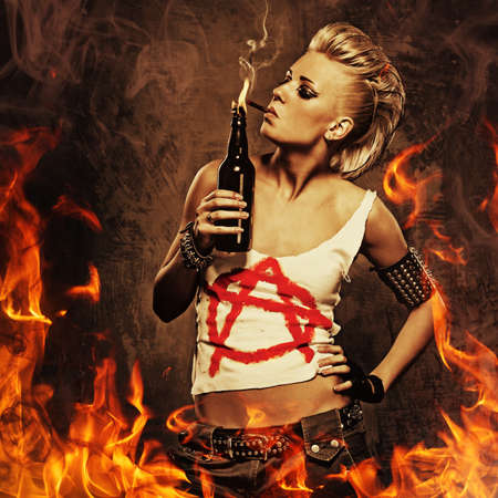 punk rock: Punk girl smoking a cigarette over fire background. Stock Photo