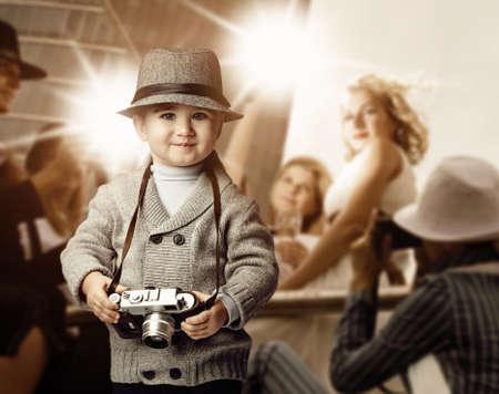 Baby jongen met retro camera over fotoshoot achtergrond.
